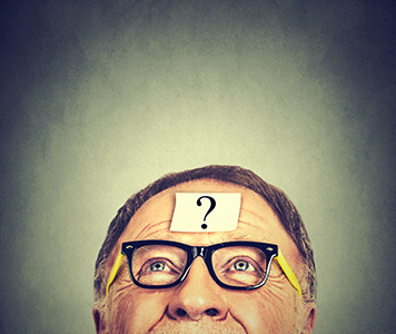 thinking senior man with question mark on gray wall background .